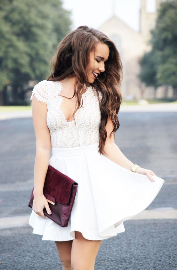 a white dress with a lace bodice and cap sleeves, a deep V cut, a burgundy clutch