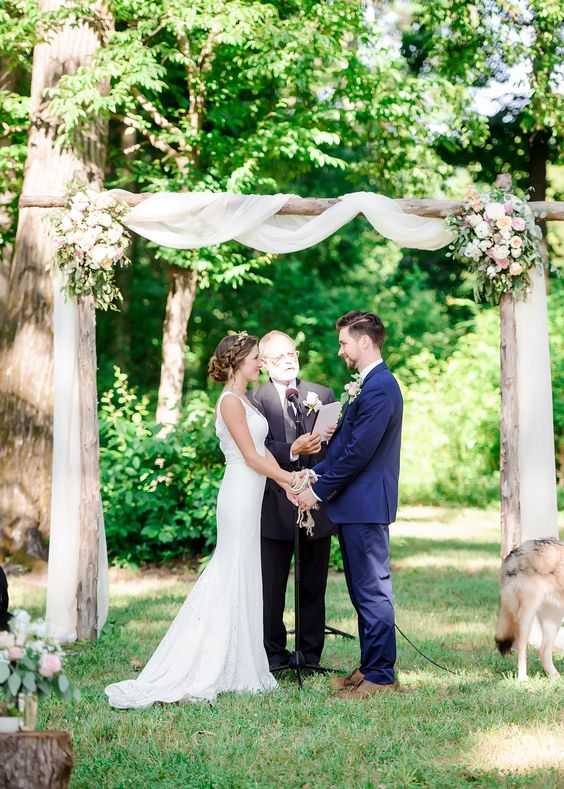 lovely wooden arch with flowy fabric and some blush flower decor