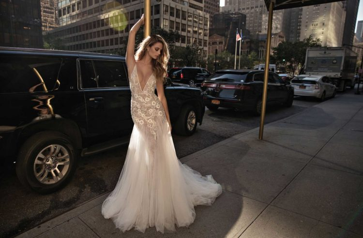 A plunging neckline wedding dress with lace appliques and a light mermaid silhouette, a tulle skirt