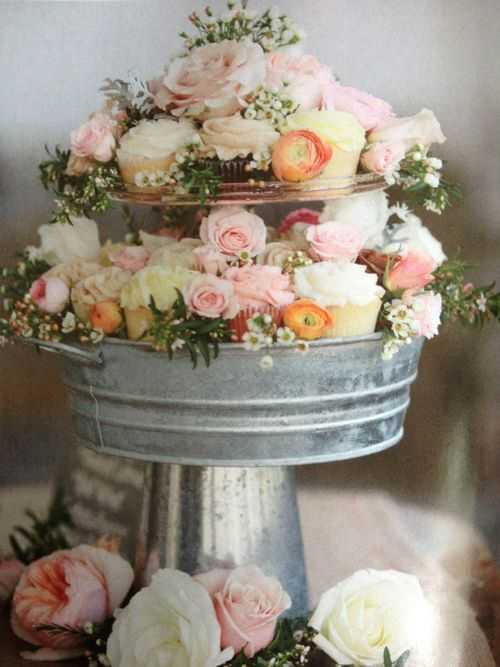 a rustic cupcake stand of a glavanized bath and bucket, filled with flowers