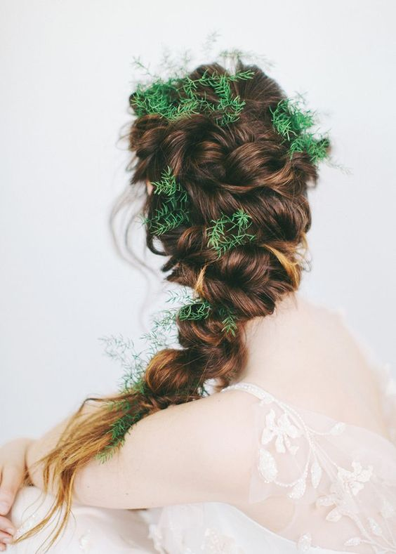a twisted braid with greenery tucked in instead of flowers