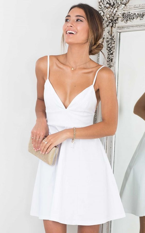 a white mini dress with a deep V cut, spaghetti straps and a jeweled clutch