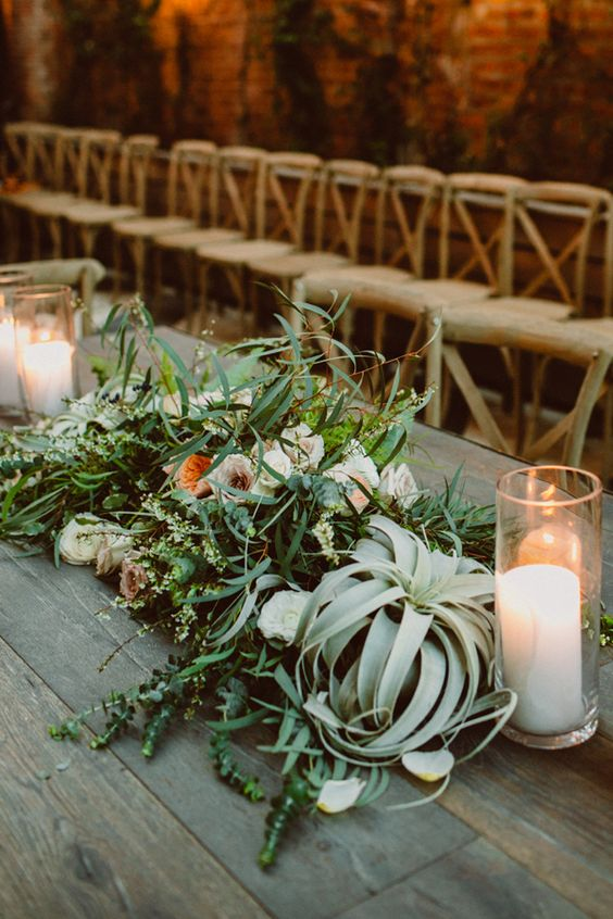 lush table decor with grass, air plants, peachy flowers, candles
