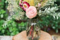 18 wood slices with a mason jar with flowers for a rustic affair