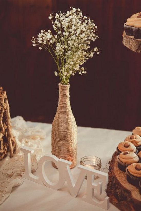 a twine wrapped bottle with baby's breath and LOVE letters