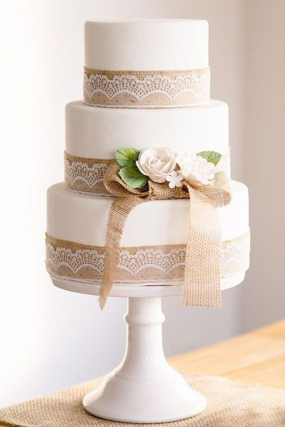 a white cake decorated with burlap and lace