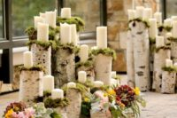 19 birch logs and cuts covered with moss and candles to create a wedding altar