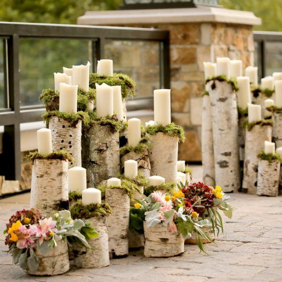 birch logs and cuts covered with moss and candles to create a wedding altar