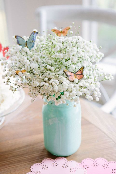 mint-colored mason jar with baby's breath and butterflies
