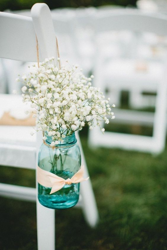 a blue mason jar with blush ribbon and baby's breath for a rustic summer aisle