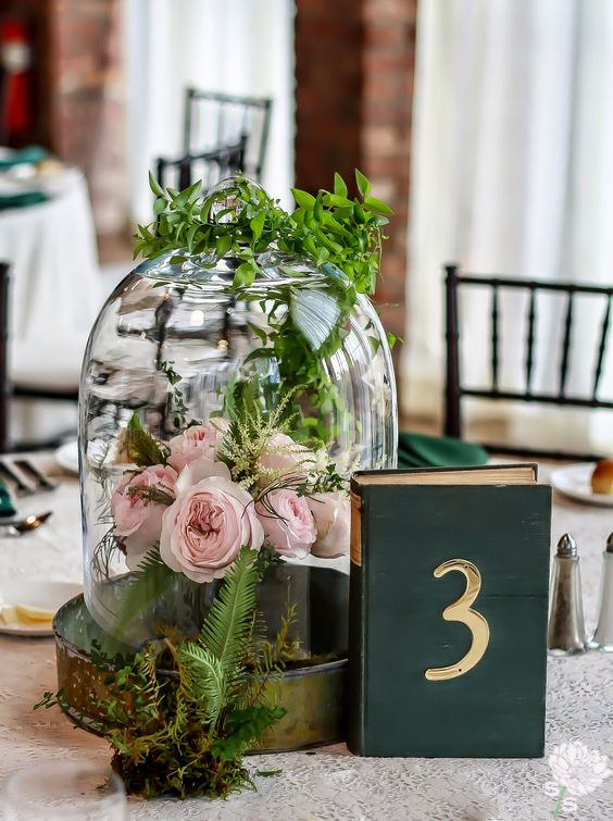 a cloche with blush peonies and greenery on top