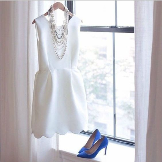 a white mini dress with a scallop hem, layered necklaces and blue heels