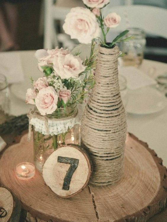 a wood slice with a twine wrapped bottle and a mason jar, flowers and a wood burnt table number