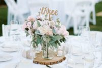 20 a wood slice with candle holders and a clear mason jar with a blush floral arrangement plus a table number