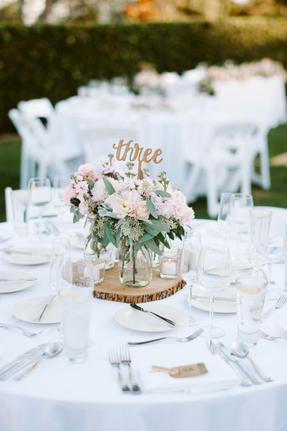 a wood slice with candle holders and a clear mason jar with a blush floral arrangement plus a table number