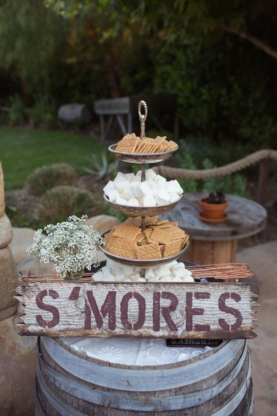 an s'mores bar on a wine barrel decorated with a simple sign