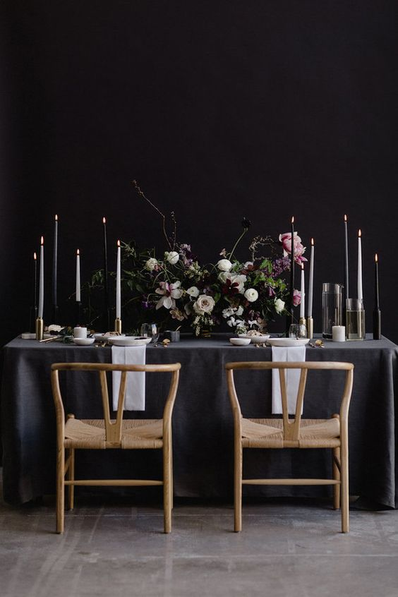 moody tablescape with black and white candles and moody textural florals