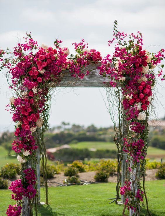 the wedding arch covered in fuchsia and white bougainvillea