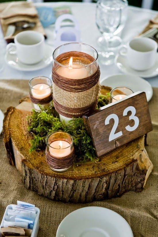 a wood slice with candle holders wrapped with burlap and yarn, a wooden table number