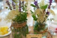 21 a wood slice with two mason jars with wildflowers and a lace table number for a rustic wedding