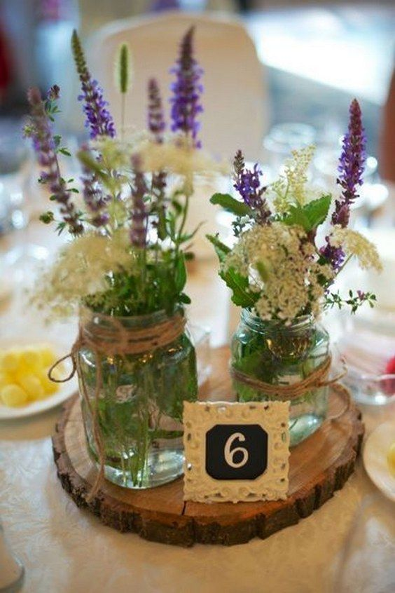 a wood slice with two mason jars with wildflowers and a lace table number for a rustic wedding