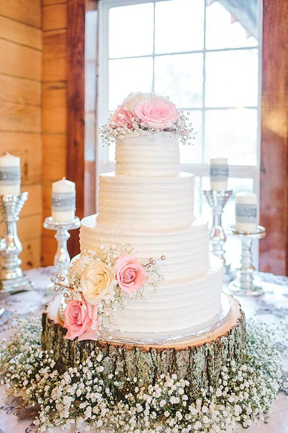 white multi tiered cake topped with pink roses and baby's breath