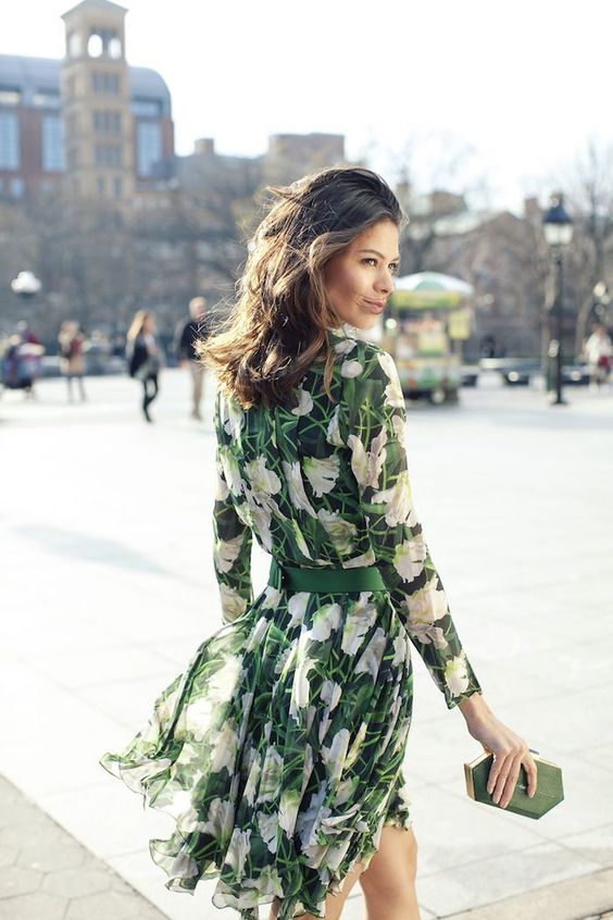 a green floral knee dress with sleeves and a small clutch