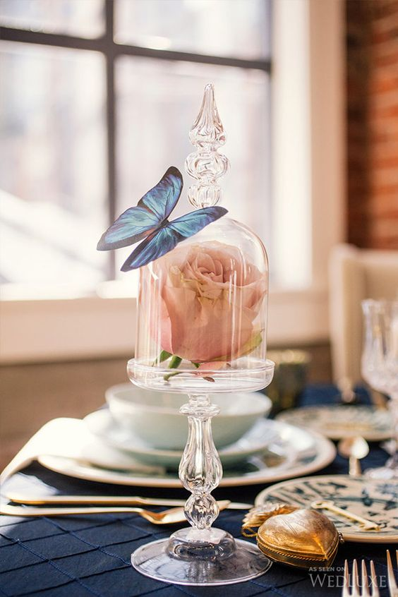 a single blush blooms in a tiny cloche with a faux butterfly