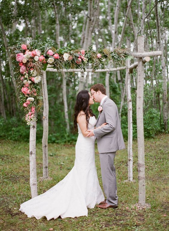 rustic wedding arch decorated with greenery and pink blooms