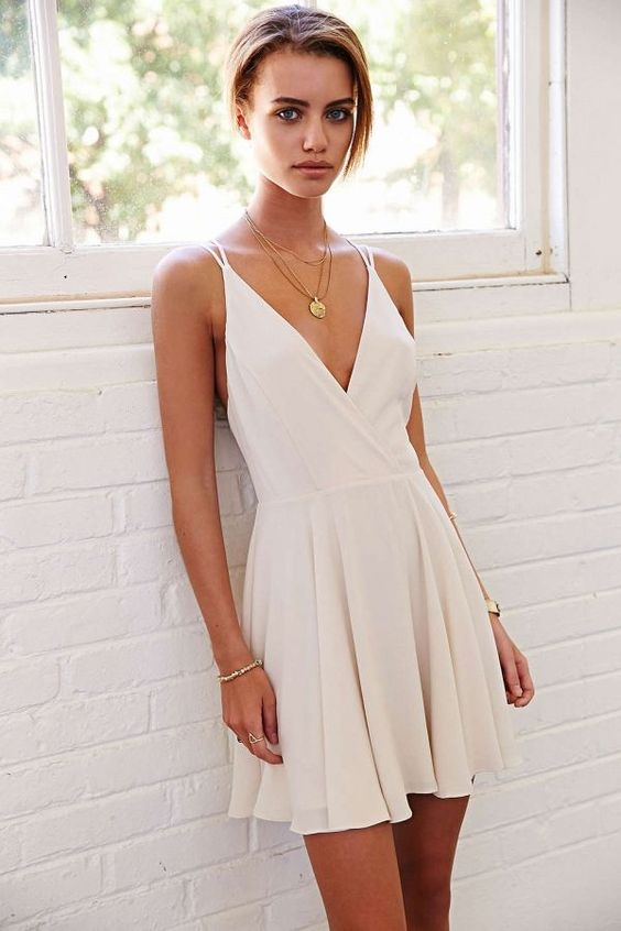 an ivory skater dress with a pleated skirt, a deep V neckline and straps