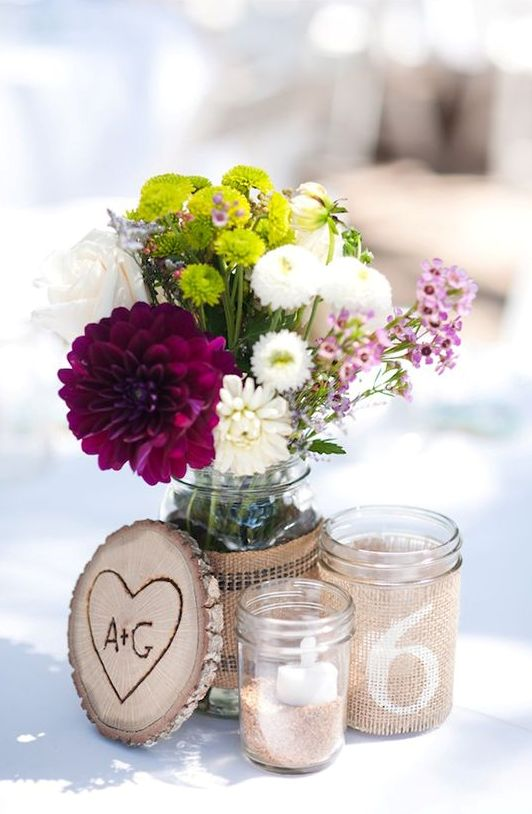 jars with candles and flowers, a wood slice with a heart burnt on it