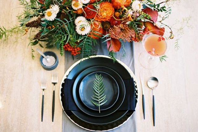 orange and red bold floral arrangement and black gold-edged plates