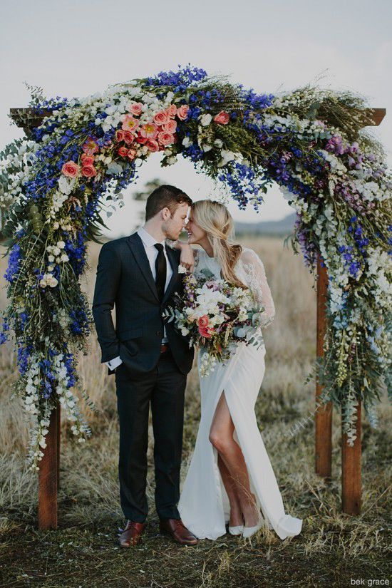 super bold wildflower wedding arch in peachy, blue and white colors