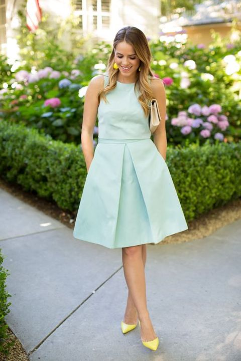 a mint knee dress without sleeves and yellow shoes and earrings