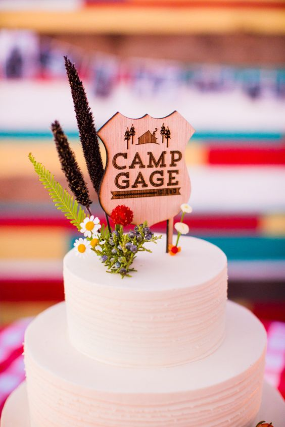 a plain white cake topped with wildflowers and a camp sign