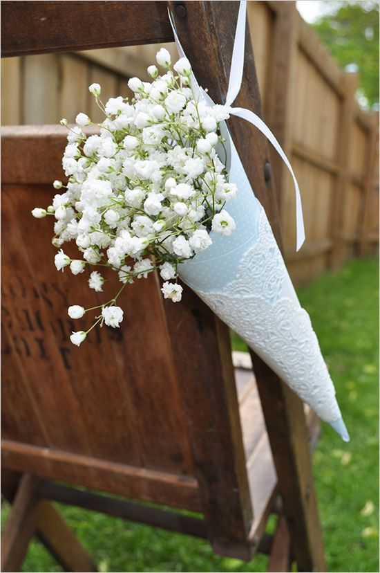 colored paper and a paper doily with baby's breath for aisle chair decor