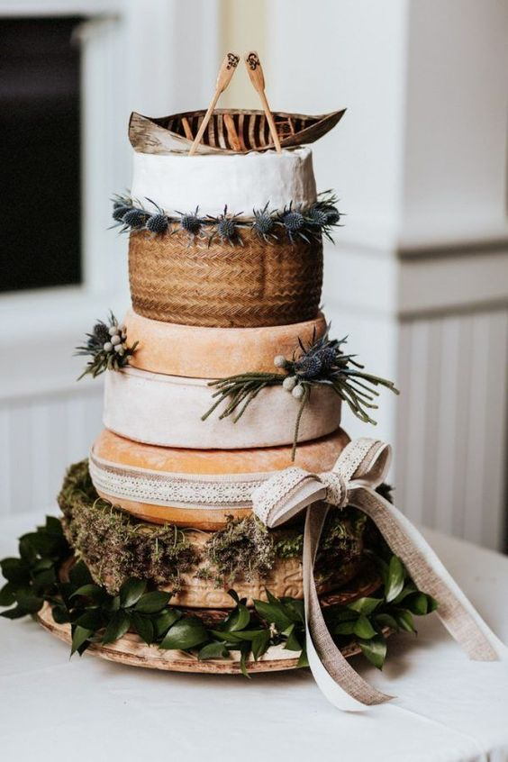 a cheese tower topped with a canoe and oars