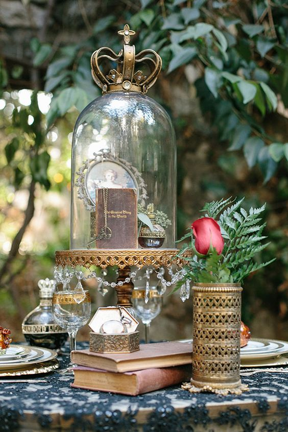 a cloche with a vintage book, key, a perfume and a framed portrait with a crown on top