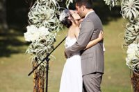 25 a wedding arch with white hydrangeas and air plants