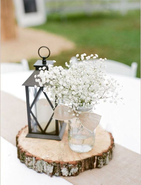 a wood slice with a mason jar with baby's breath and a lantern