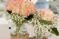 25 mason jars wrapped with burlap and with floral arrangements, twig hearts