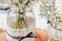 26 mason jars wrapped with lace and with navy bows plus baby's breath