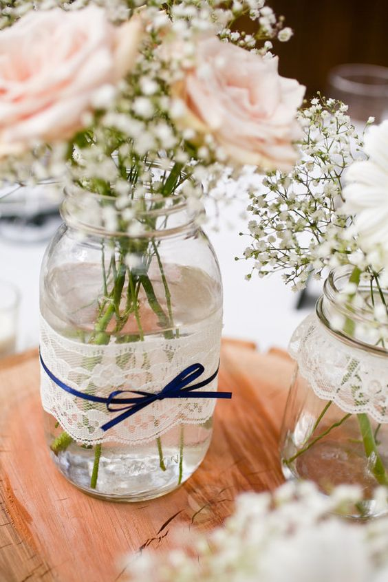 mason jars wrapped with lace and with navy bows plus baby's breath