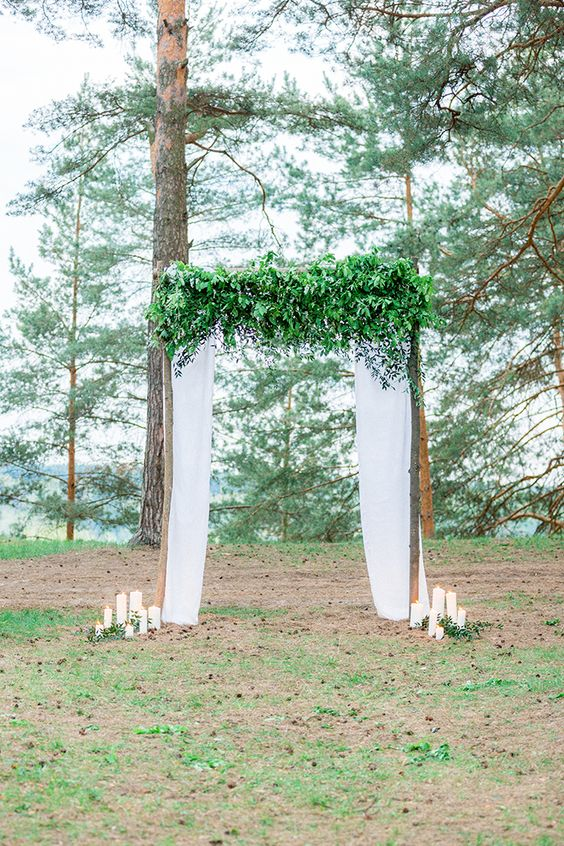 wooden branches wedding arch with white curtains and lots of green leaves