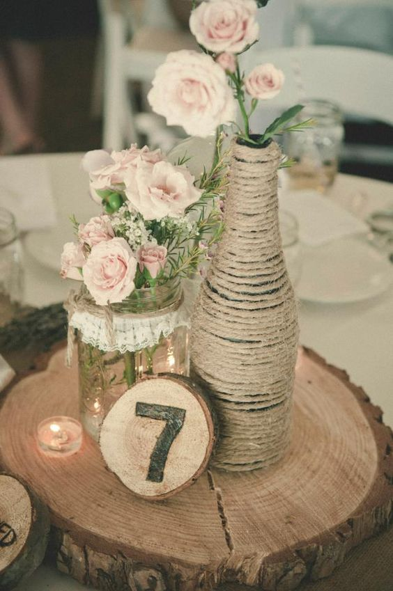 a mason jar with lace and a twine wrapped bottle with blush flowers on a wooden slice