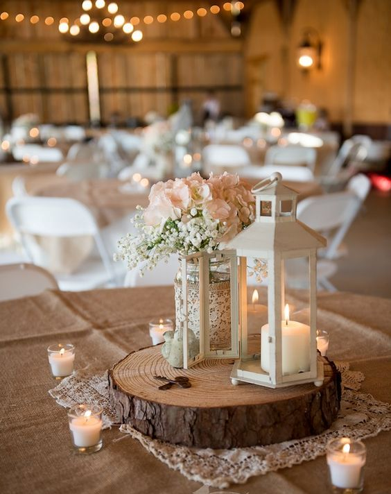 a white lantern with candles, a mason jar with burlap and lace, white blooms