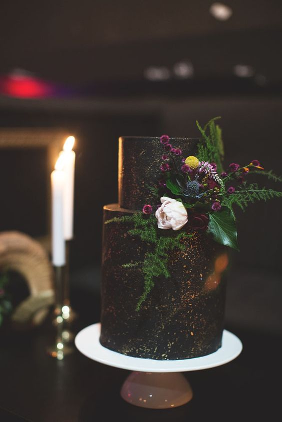 black and glitter wedding cake with greenery and blooms