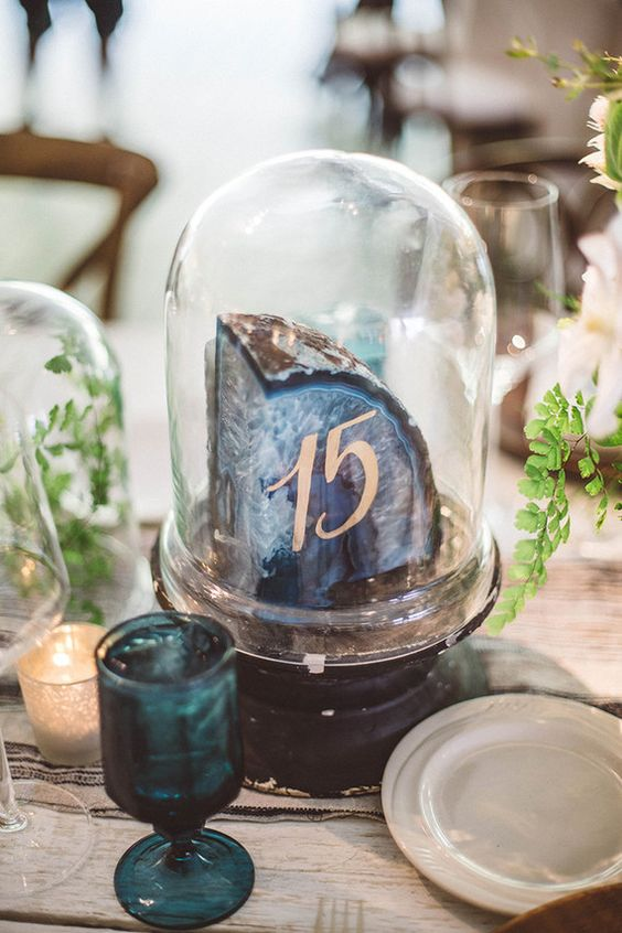a giant agate slice with a table number in a cloche is a trendy idea