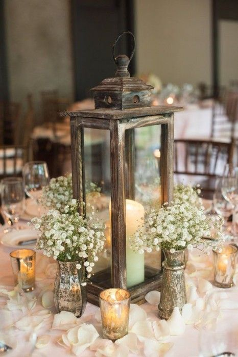 a rustic lantern of wood, candles around and vintage vases with baby's breath