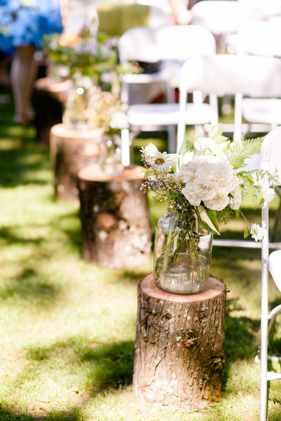 log stands with greenery and neutral flowers for a rustic summer aisle